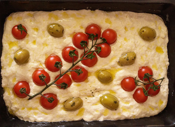 Simple Focaccia : olives, cherry tomatoes, fresh thyme or rosemary and olive oil on golden crispy focaccia bread give you the best experience of cucina povera !